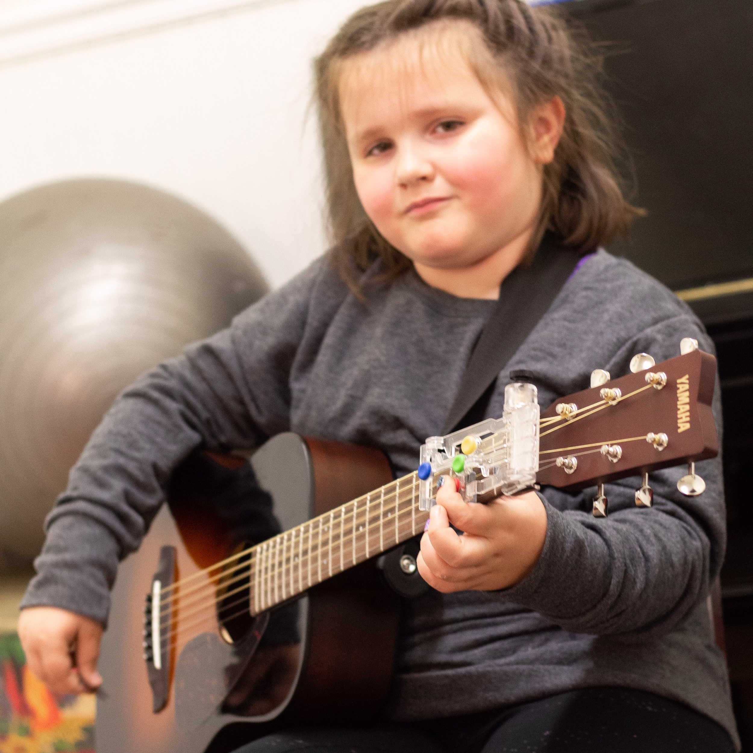 A Mella Music Therapy client works with her ChordBuddy on the guitar.