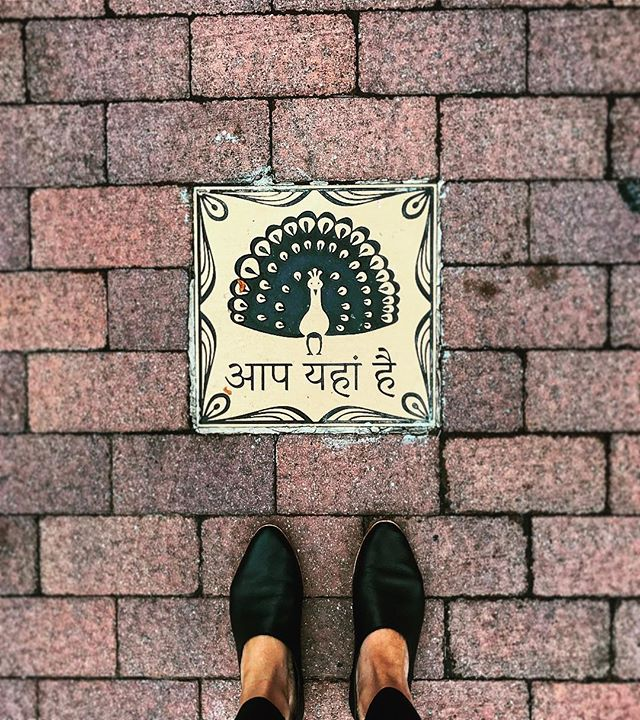"""YOU ARE HERE"" (hindi translation: aap idhar hai) A great reminder to BE PRESENT. 🙏🏽 #here #now #beherenow #bepresent #meditation #mindfulness #om #omzone #ihavethisthingwithfloors #art #streetart #pavement #brick #hindi #india"