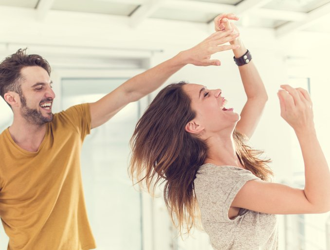 Cheerful couple having fun while dancing together