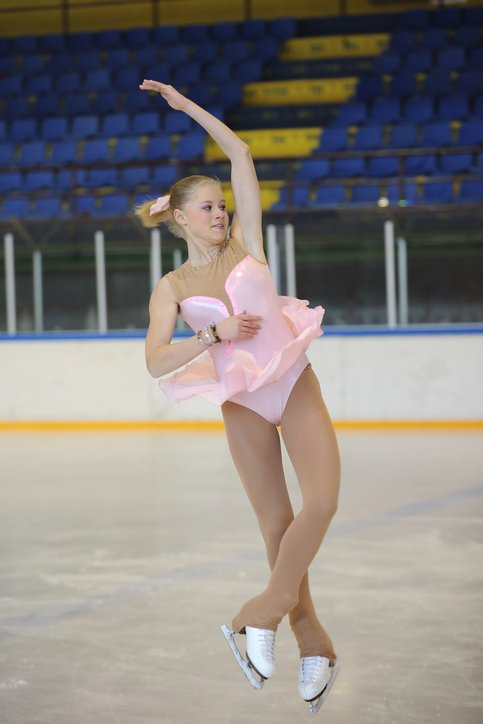 Ice dancer in pink shown spinning on ice inspired by Ballroom Dancing