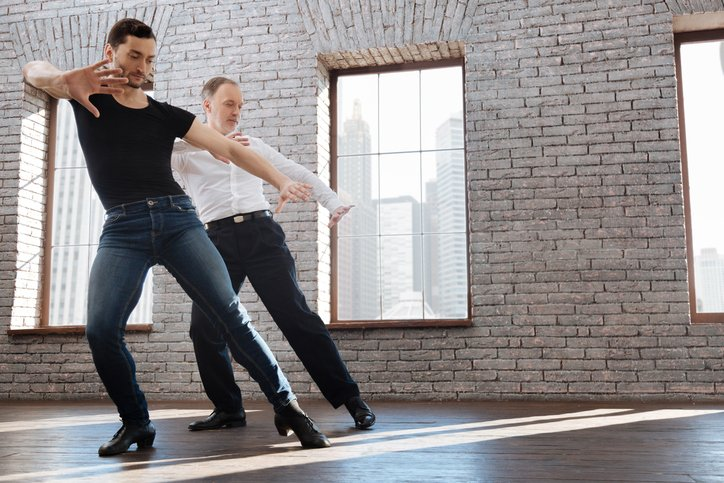 A charismatic coach teaching his student to dance
