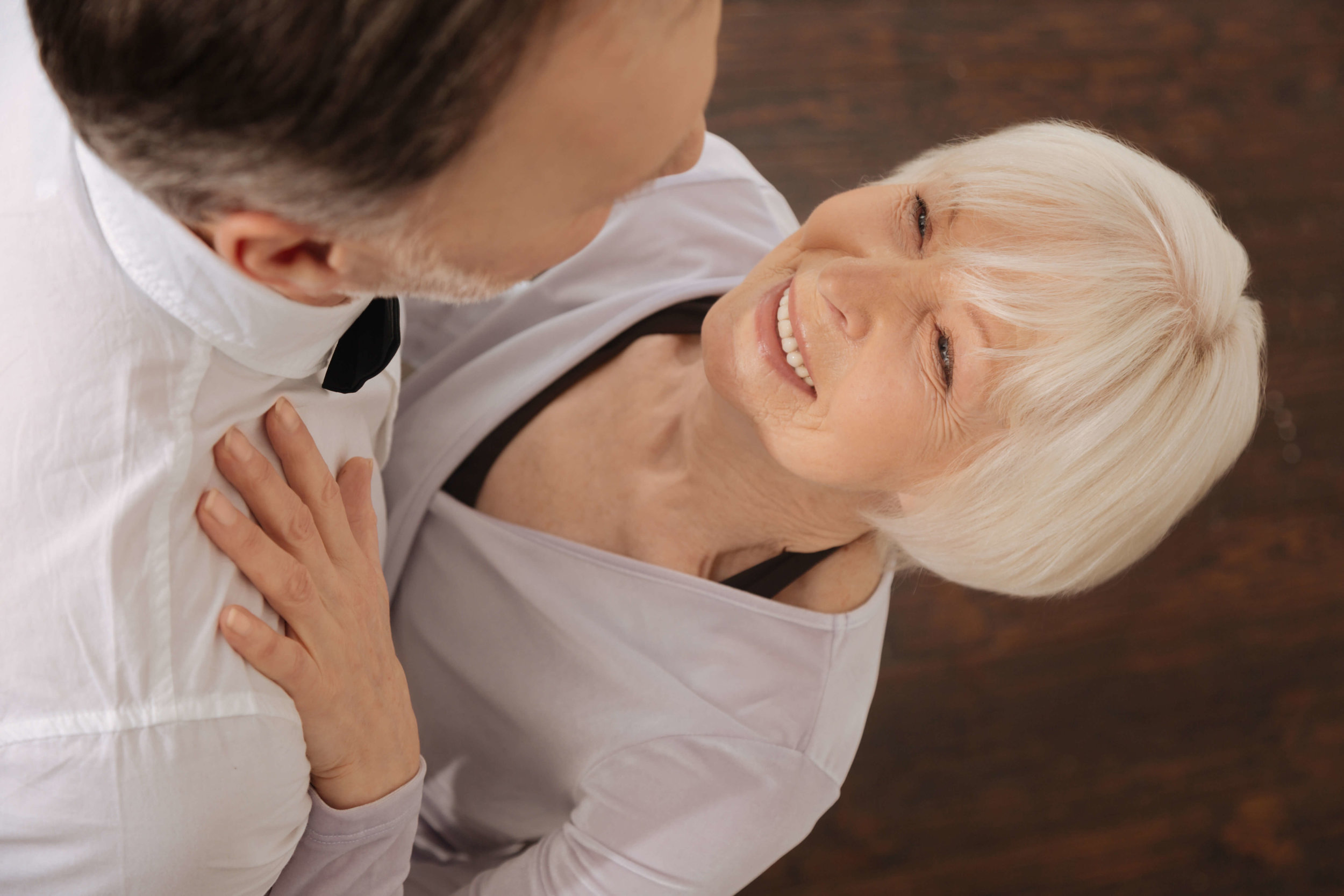 A senior couple taking ballroom dance classes together. Woman looks into man's eyes