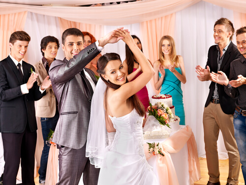 Groom impressing his bride and friends with a twirl after taking wedding dance classes
