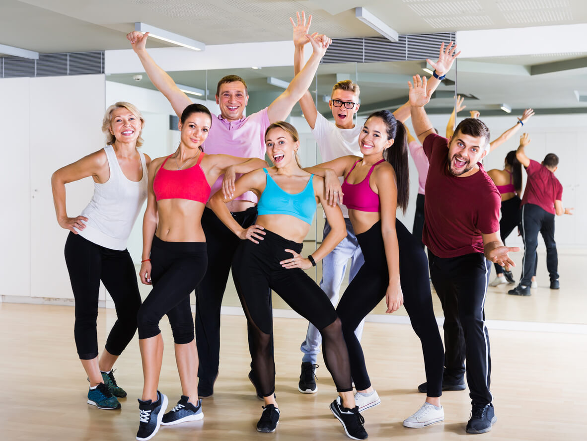 Happy people posing in a ballroom dancing studio before lessons