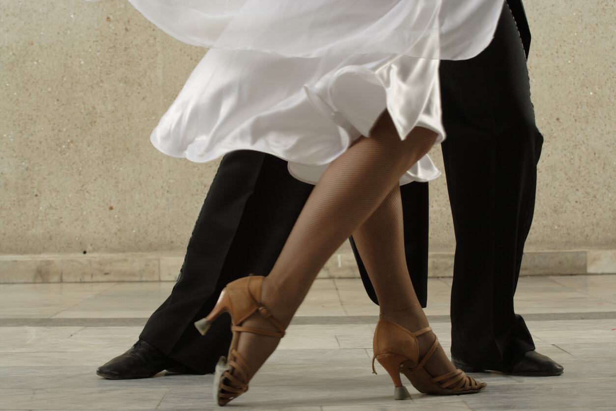 Two To Tango. Dancing couple doing the tango in a dance lesson shown from the legs down