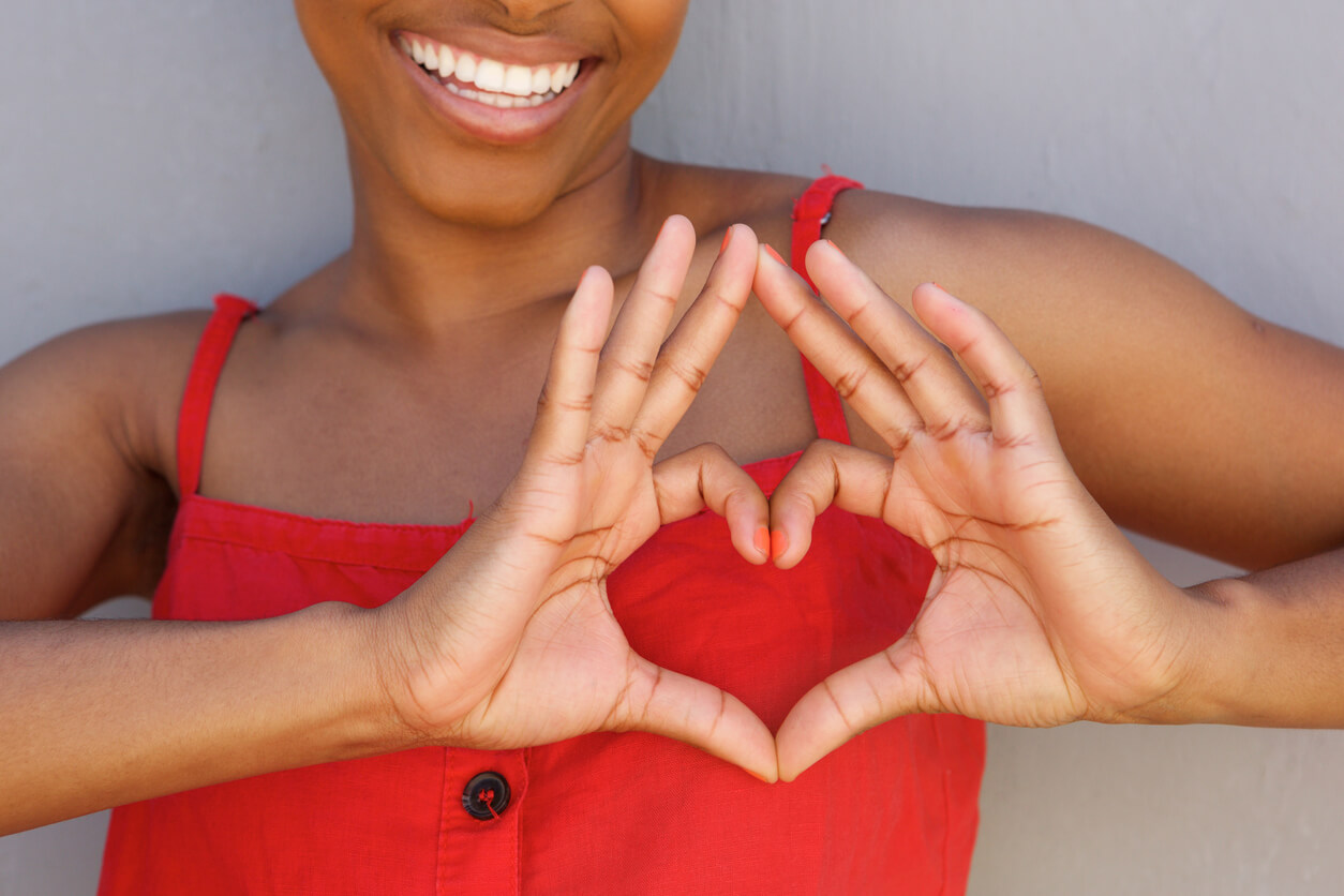 Health Benefits of Ballroom Dancing.Close up young woman smiling with heart shape hand sign. Health Benefits of Ballroom Dancing concept