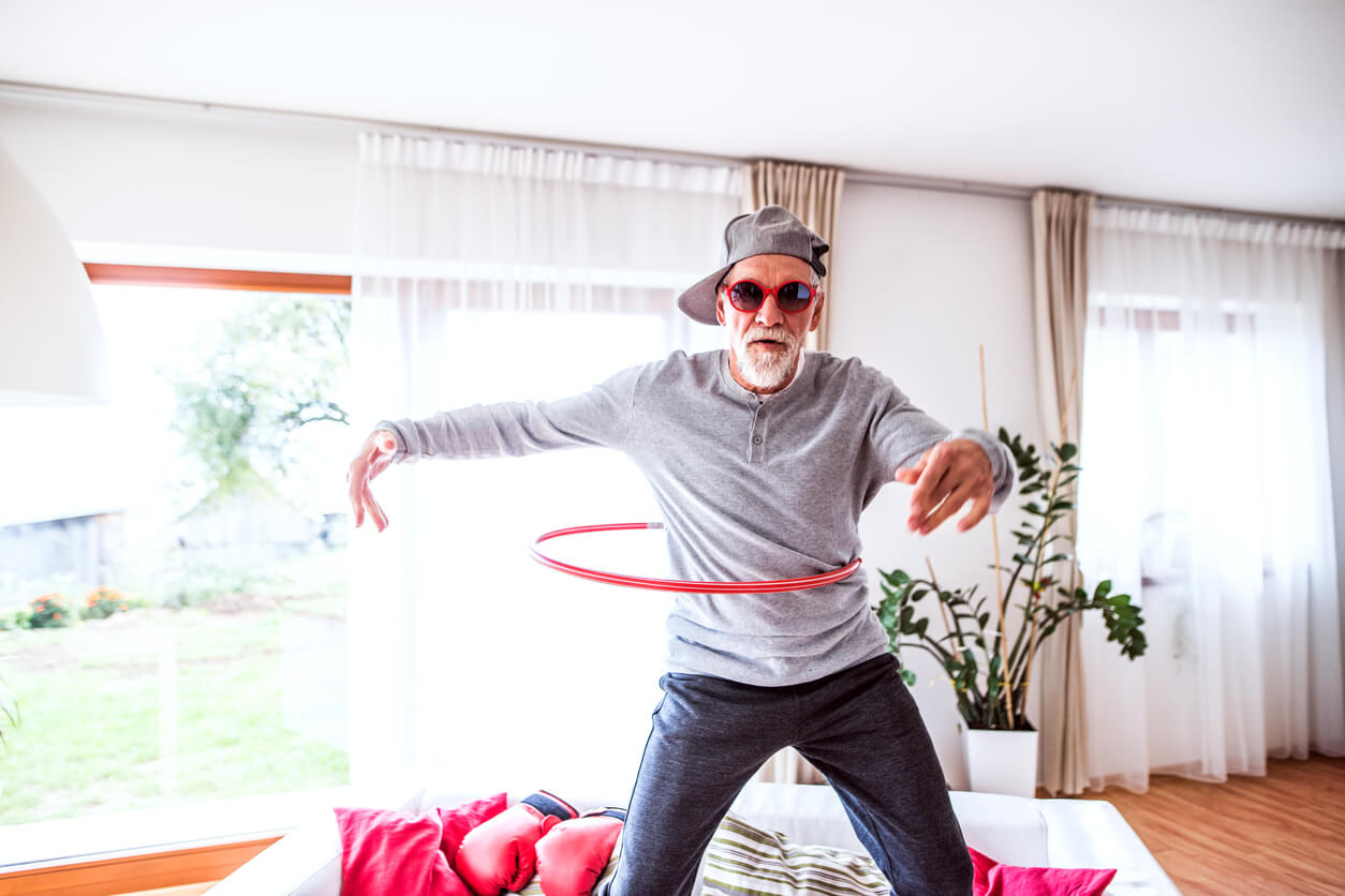 Dance Your Way Back to Youthfulness. Senior man having fun at home hoola hooping. Dancing your way back to youthfullness