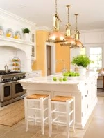 This kitchen has been painted with Beeswax, by Pratt & Lambert. The style is modern country - I love the use of copper and brass over sized pendants over the island. You can see how the colour is repeated in decor above the stove. Well Done!