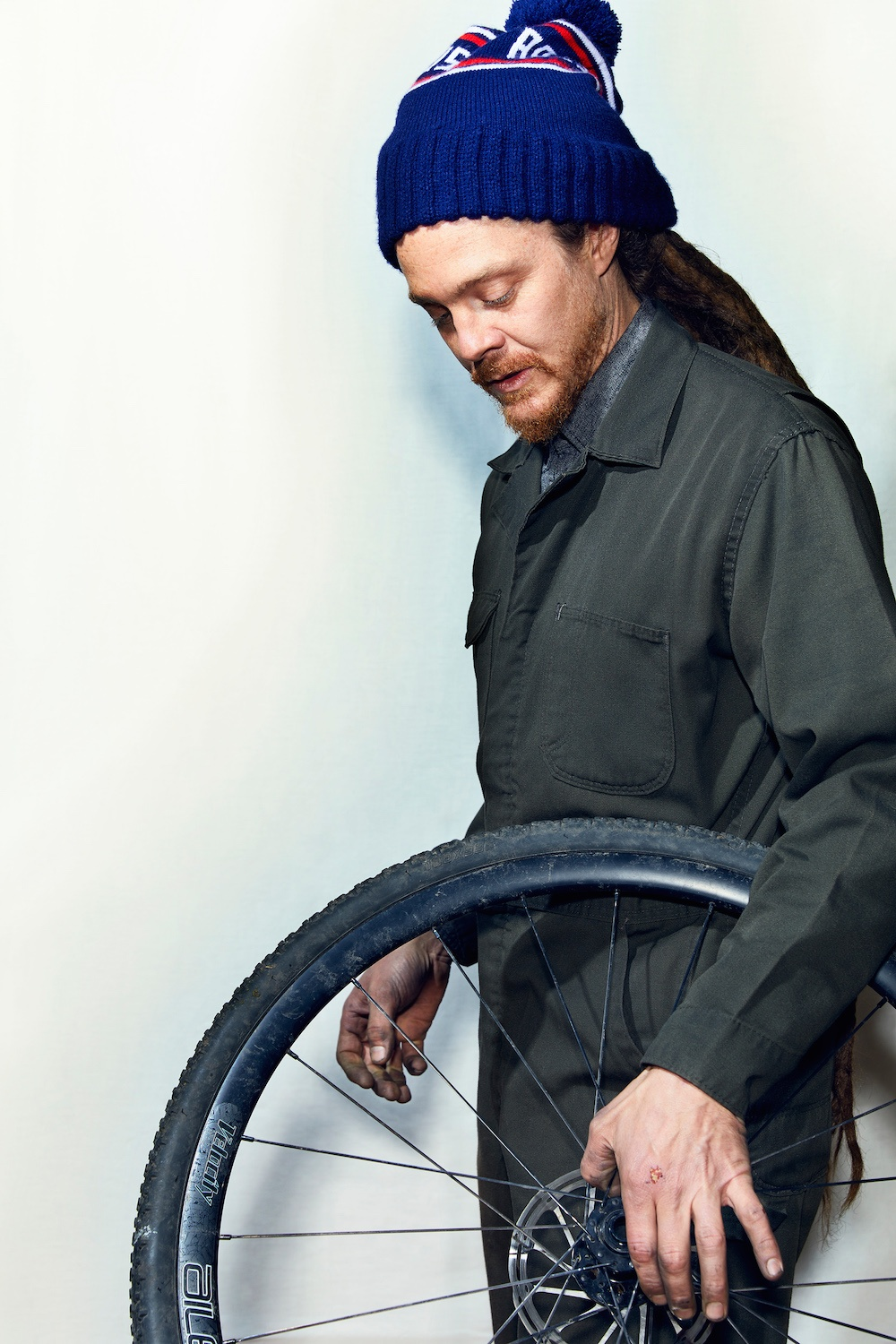 Bike-mechanic-holding-wheel-one-hand.jpg