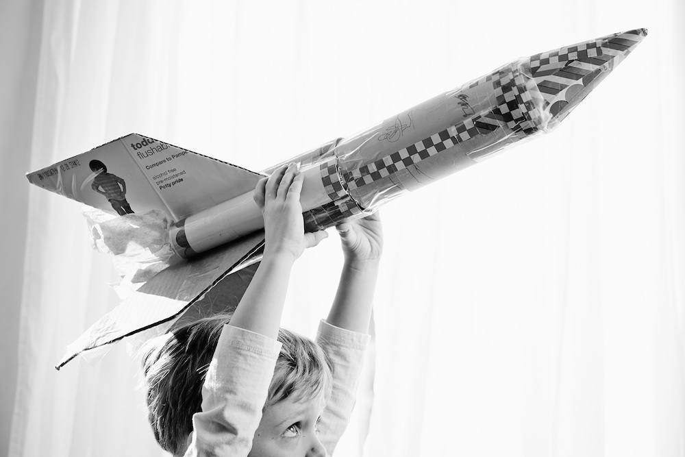 Child-playing-paper-rocket-ship-black-white.jpg