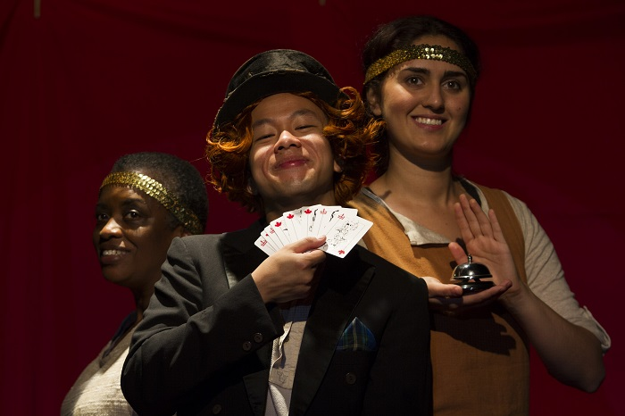 William Lyon Mackenzie (Matthew Gin), with help from his assistants Marcia Johnson (left) and Parmida Vand uses his magical deck of cards to explain the relationships in the Family Compact, in 1837: The Farmers' Revolt at the Blyth Festival. Directed by Gil Garratt. Creative team: Beth Kates, set, projection and lighting designer; Gemma James Smith, costume designer; and Deanna H. Choi, sound designer and music composer. Production stage management: Heather Thompson and Katerina Sokyrko.. Photo credit: Terry Manzo.