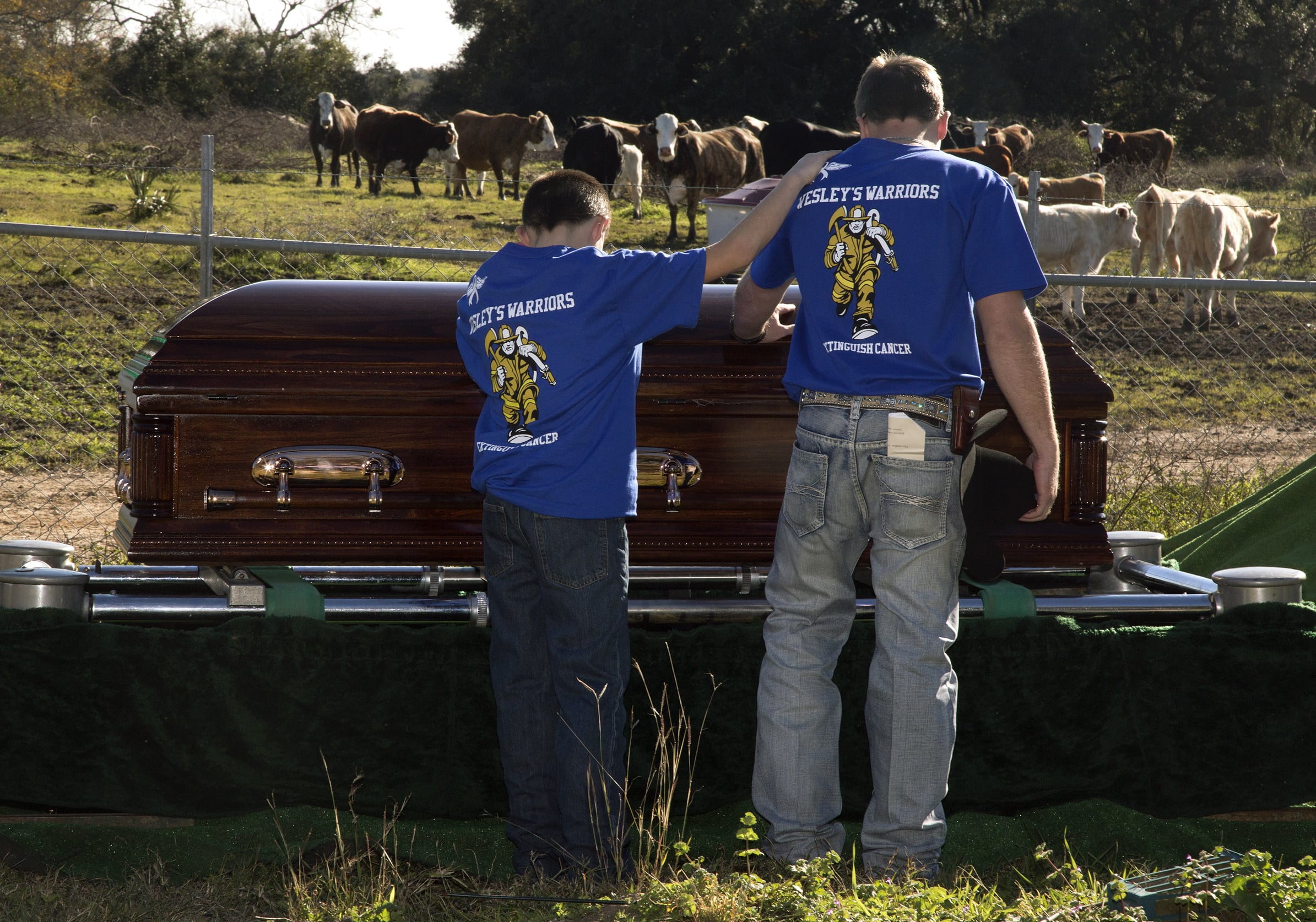 Mourners touch the casket of John Wesley Hendry on Tuesday, January 12, 2016, at Red Bluff Cemetery in Lolita, TX.