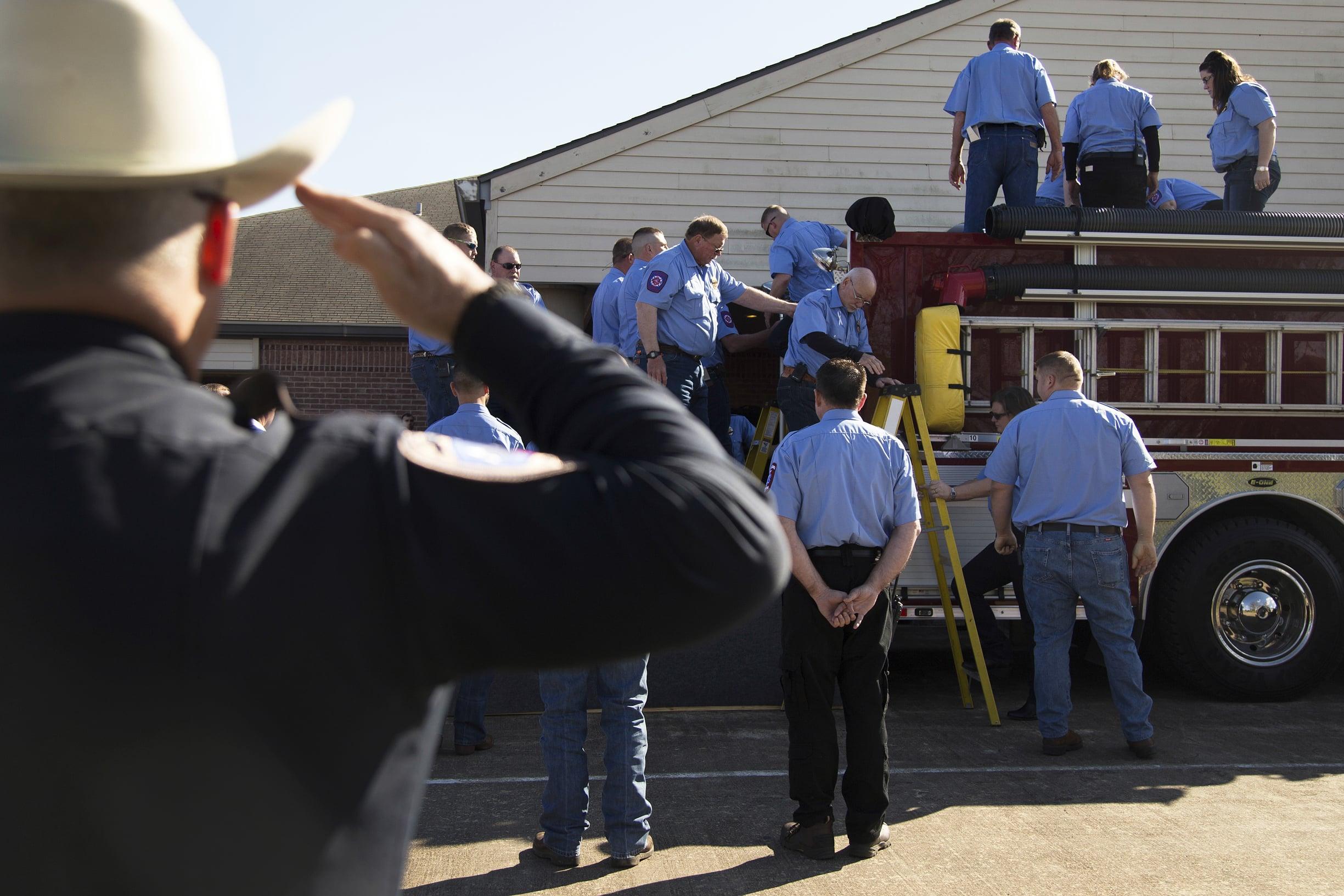 Henry's casket is loaded onto a firetruck outside the Oaklawn Funeral Home Chapel in Edna, TX.