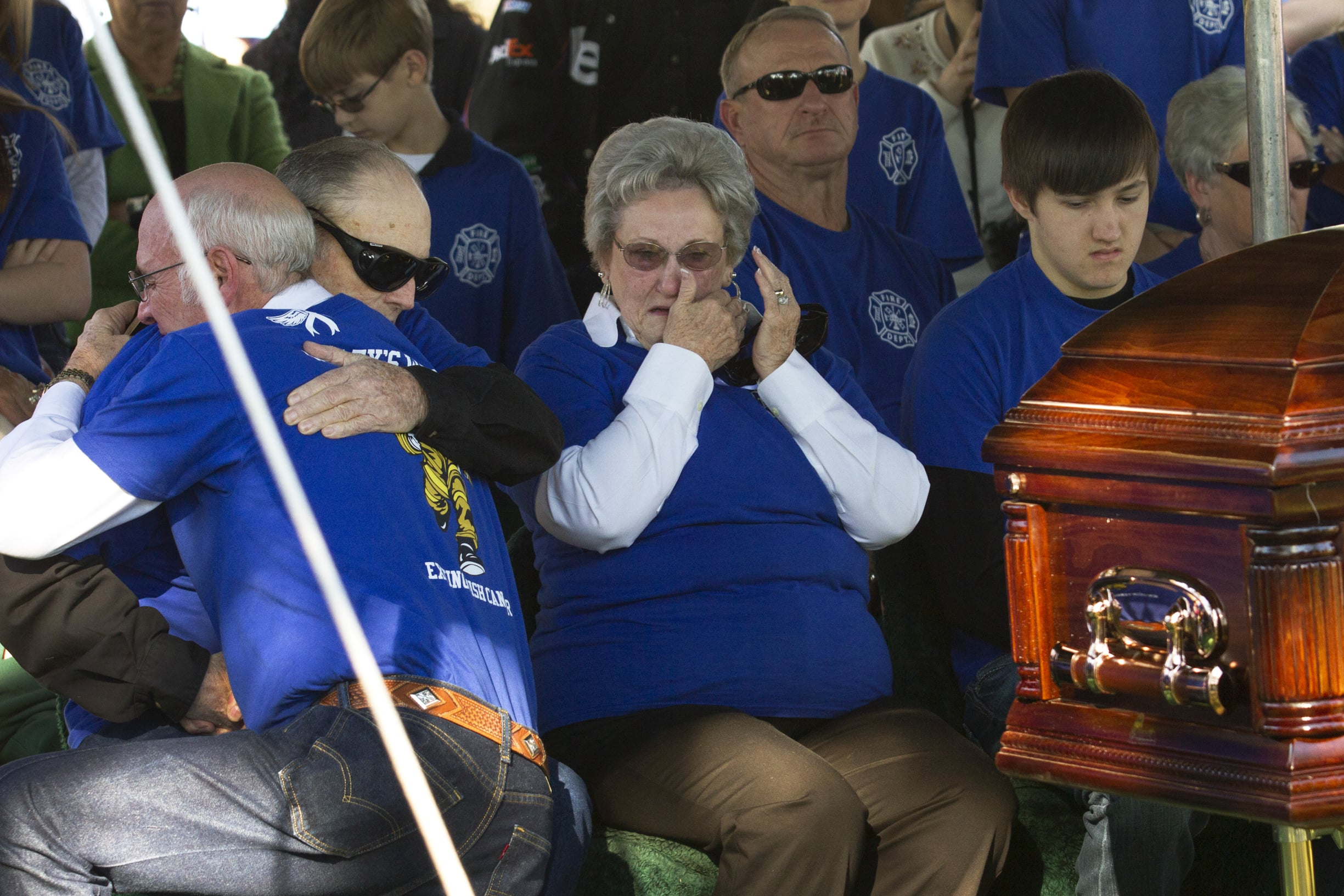 Harry Conn Hendry, left, and Betty Conn Hendry, right, the parents of John Wesley Hendry, are hugged by mourners.
