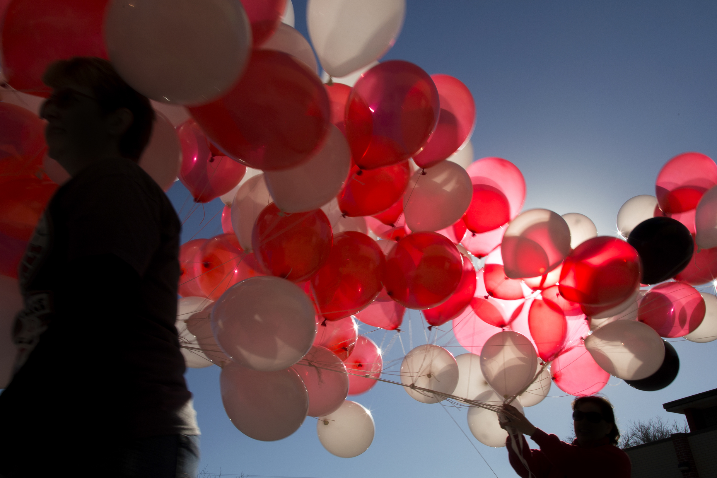 Volunteers carry balloons from inside the school to the football field.