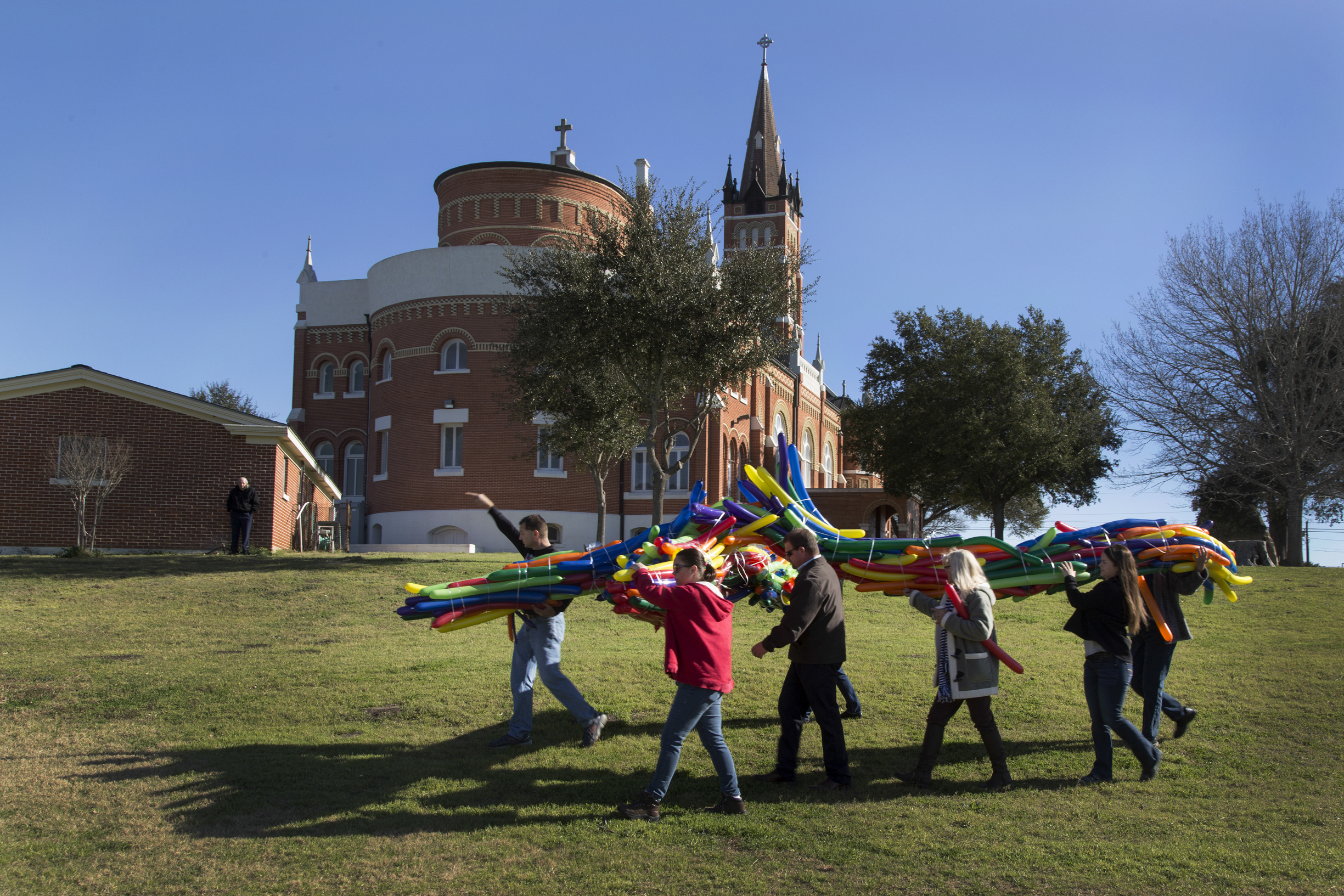 A cross made up of long, thin balloons is carried past the church to be released with hundreds of smaller ones. Larger ballons filled with helium were tied to the cross before its release.