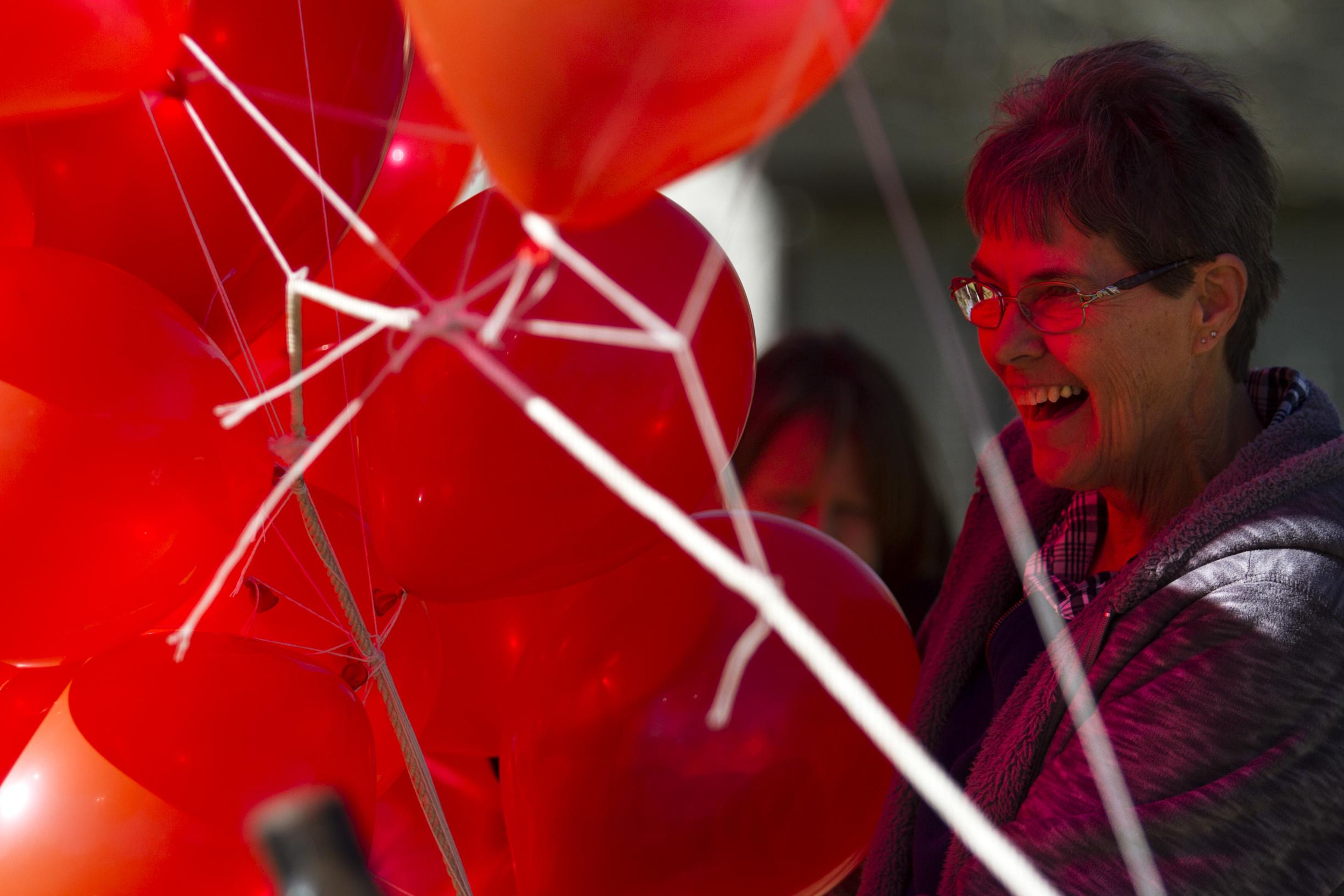 Volunteer Barbara Klozik helps tie down balloons outside near the football field.