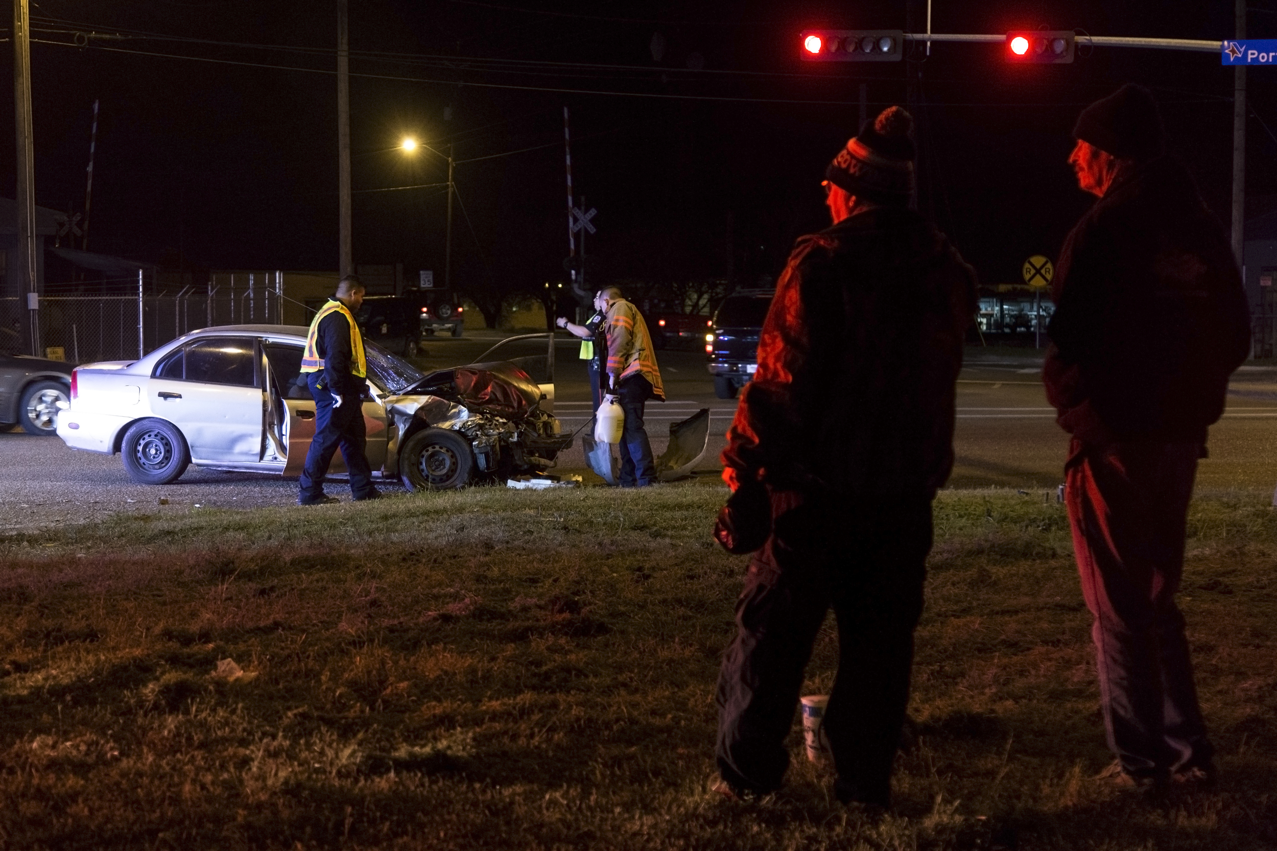 Bystanders watch the clean up the accident at the intersection of Ben Jordan Street and Port Lavaca Drive.