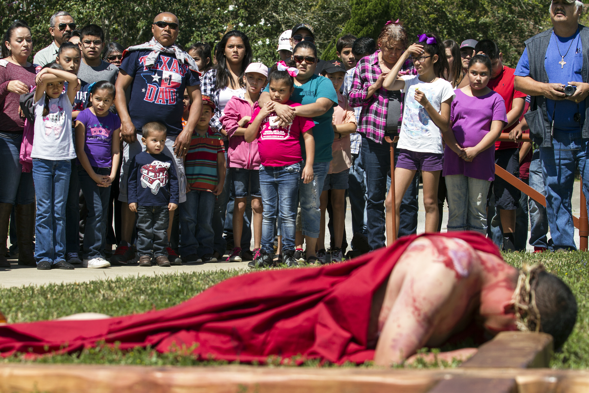 "Baltasar Godinez, 21, of Victoria, lies down next to the cross while portraying Jesus during a reenactment of the crucifixion of Christ on Friday, March 25, 2016, at Our Lady of Sorrows Catholic Church in Victoria, TX. ""Father chose me. I guess I fit the role... The hardest part was staying completely still when I died,"" Godinez said."