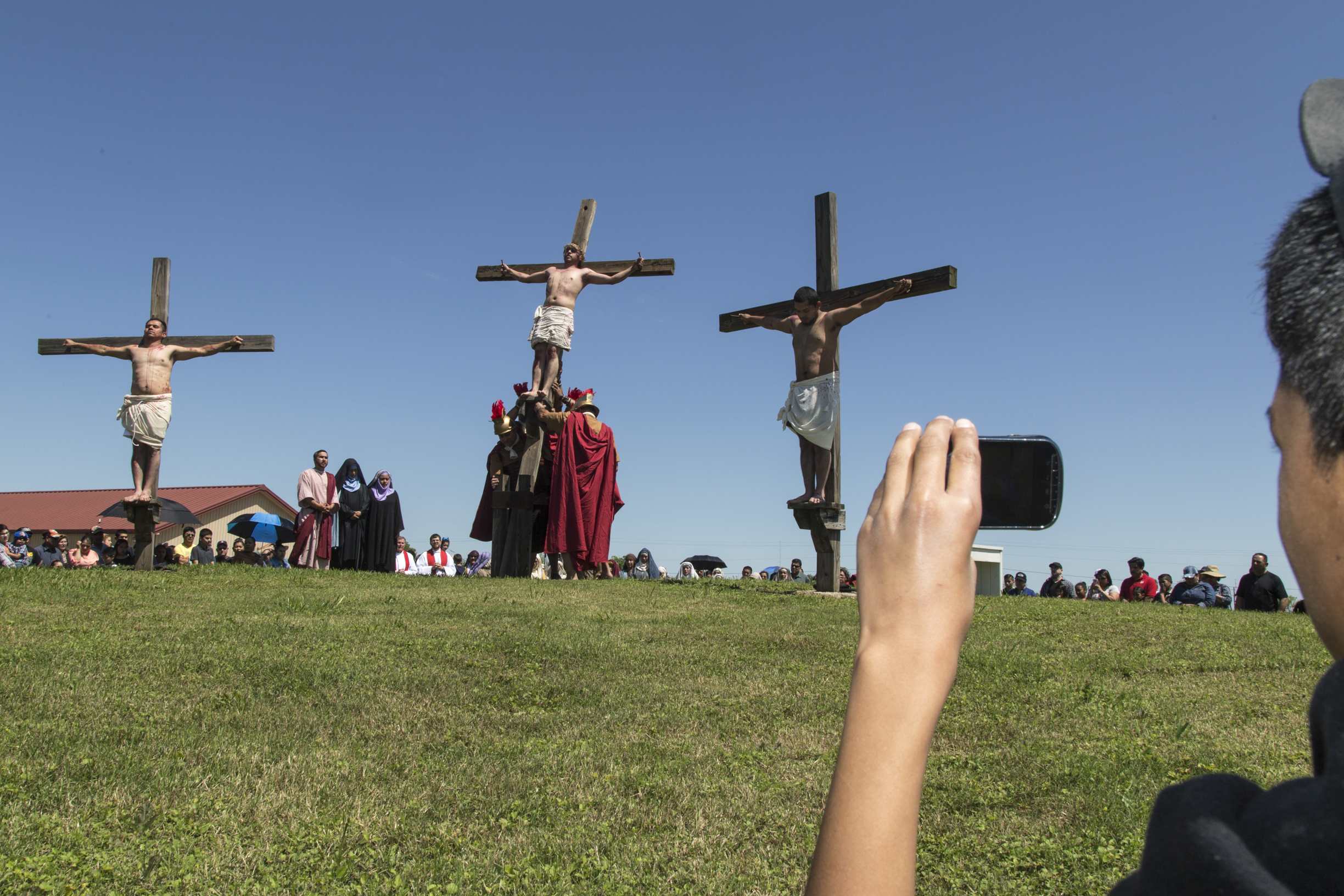 Spectators film and take photos of the reenactment of the crucifixion of Christ.