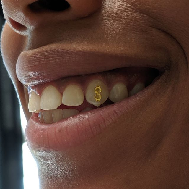 Cool gold dollar sign I did! 🦷✨ Gold options in stock are limited, but we can always order more in. Mention in your email what you were looking for! Email info@thetattooery.com for appointments . . . #toothgem #toothgems #toothjewelry #dentaljewelry #goldtoothjewelry #goldtoothgems #designersmile #smilemakeover #toothbling #twinkles #mdtoothgems #dctoothgems #dmvtoothgems #thetattooery
