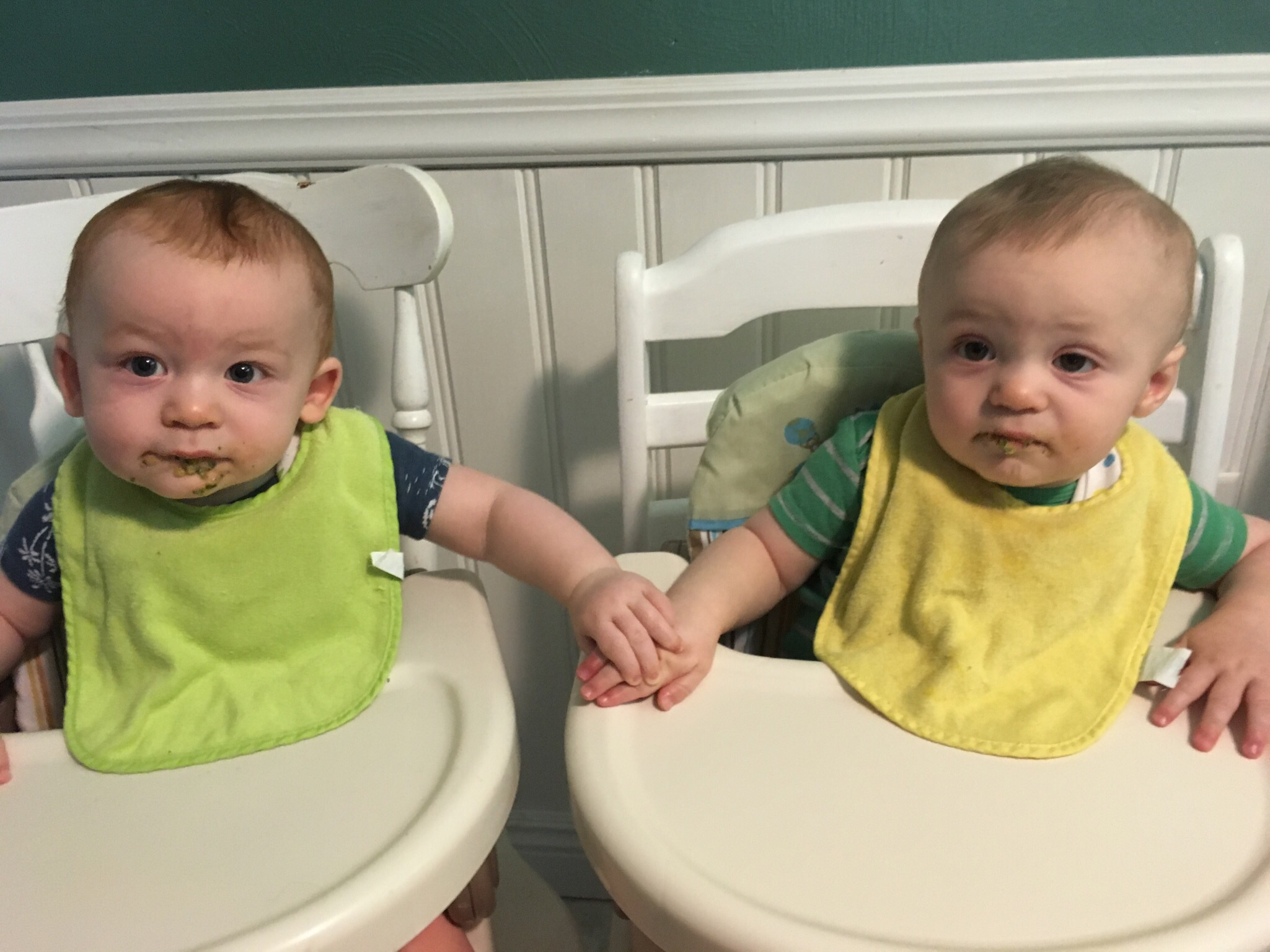 Joshua and Julian with food covered mouths, holding hands