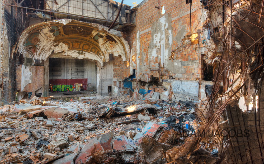 The remains of an old curtain in the foreground leading into the main seating area of the theatre.