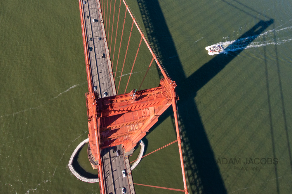Looking straight down on the South Tower of the Golden Gate Bridge in San Francisco as a boat passes through the Bay.