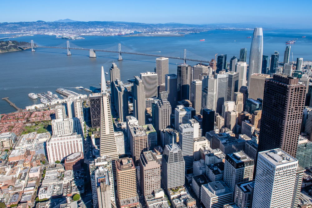 An aerial photograph of the San Francisco financial district including the SalesForce Tower, Transamerica Building and Bay Bridge taken in March 2019. A fast shutter speed and leaning slightly out of the helicopter ensured that this image remained totally sharp.