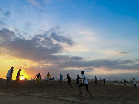 Omani lads playing soccer at sunset