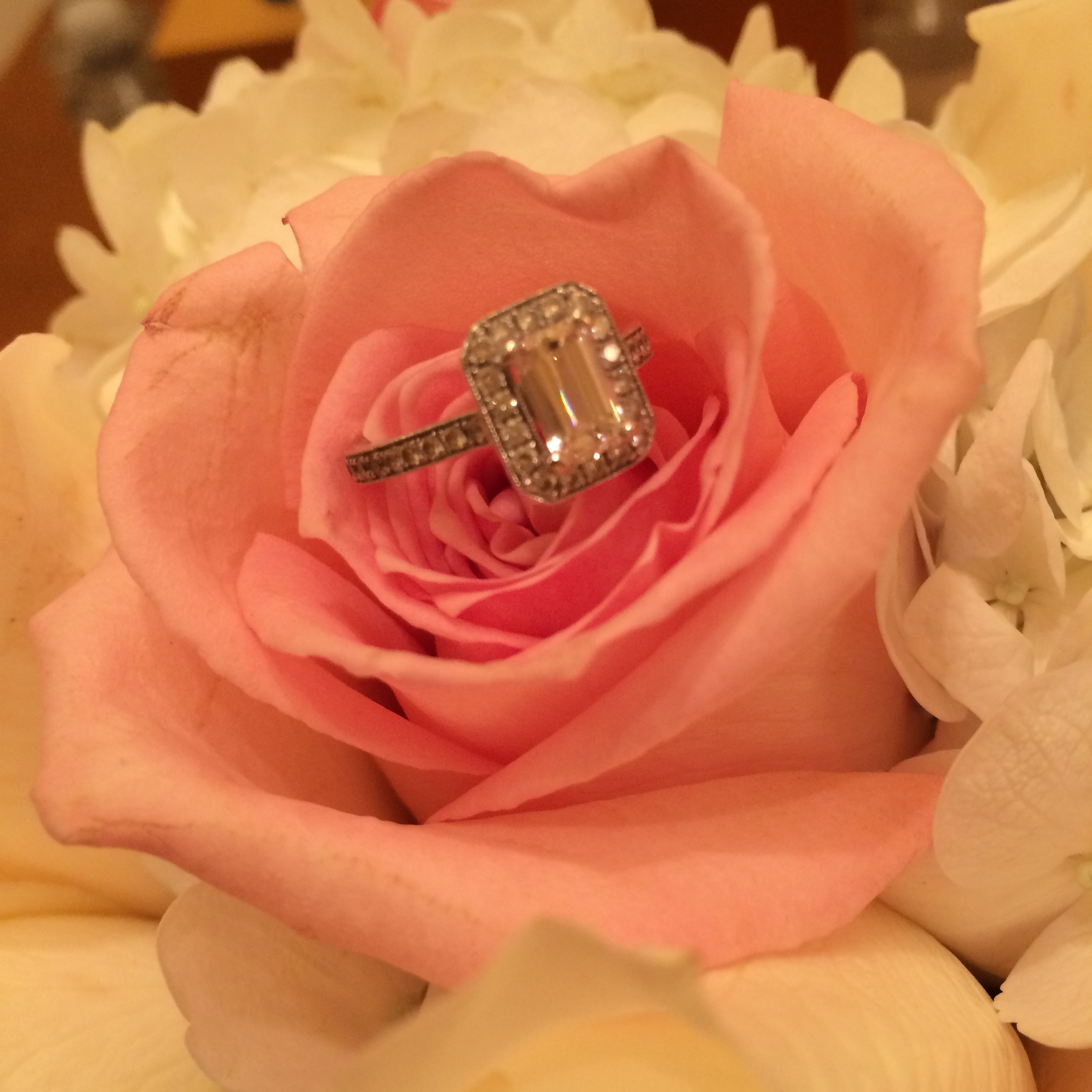 Michele's emerald cut engagement ring with halo sat nestled in her bridal bouquet.