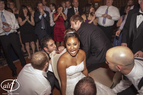 The Hora, a traditional Jewish Dance, involves lifting the bride and groom up on chairs. Then, they both grab the same napkin and are hoisted by their guests.