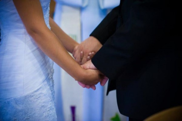 Clasping hands while saying their vows. Photo by Lighthouse Photography.