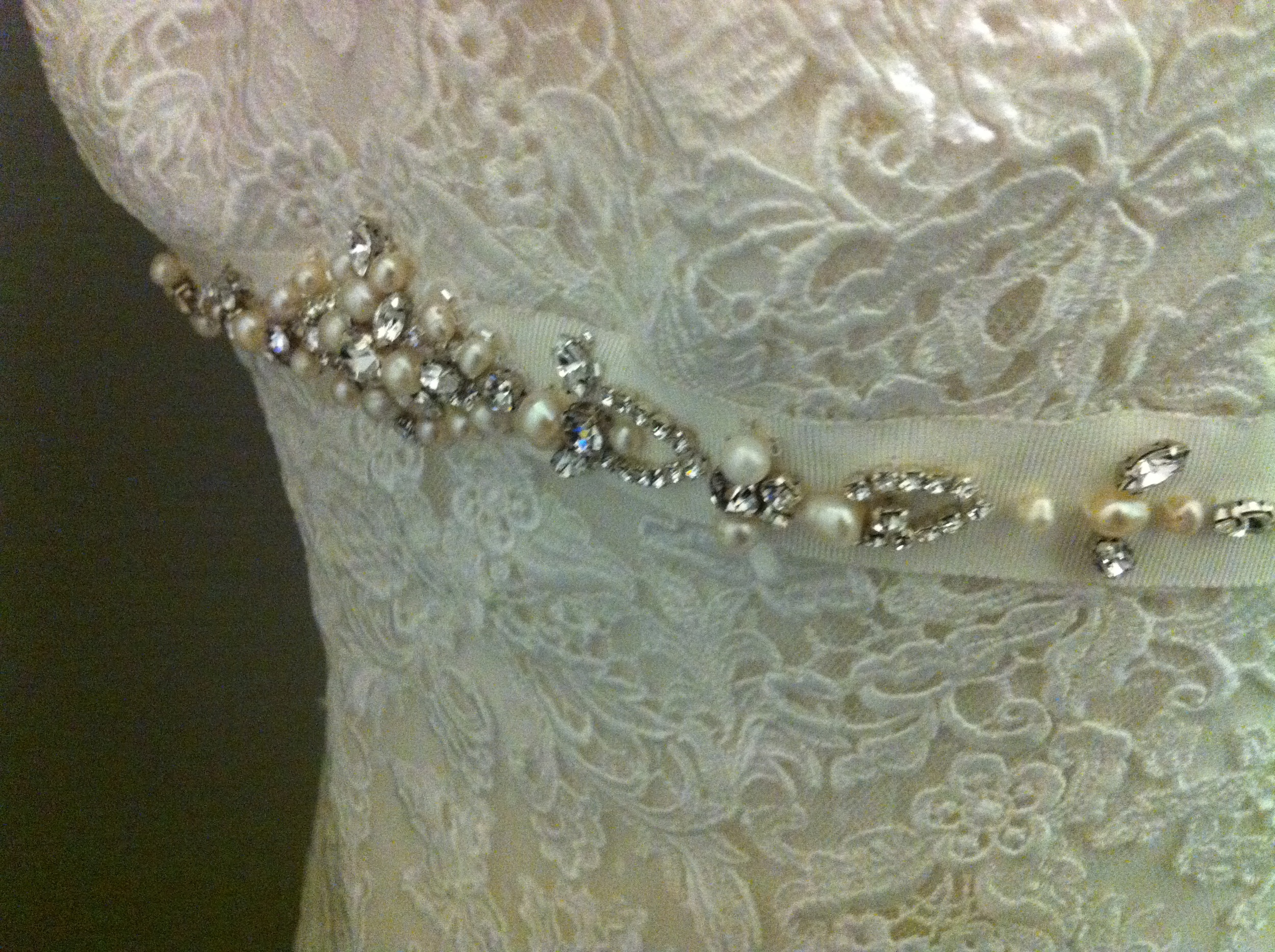 Celia's lace wedding dress was ivory and featured a jeweled accent belt at the bustline.