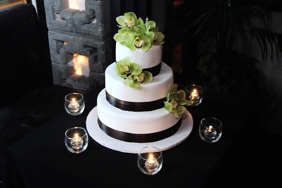 The three tiered cake was wrapped in white fondant and decorated with fresh cymbidium orchids.
