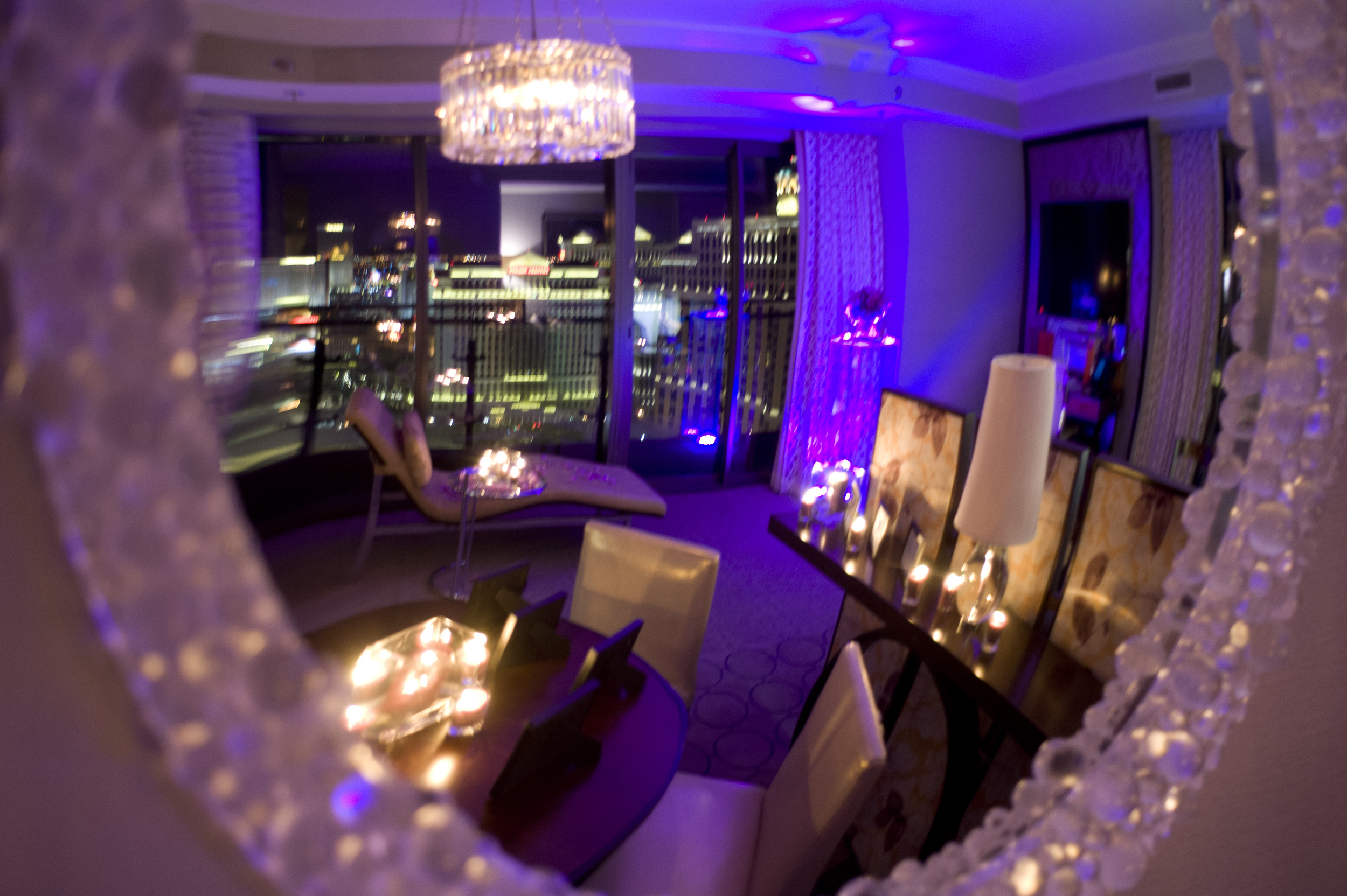 An overview of the room and seen through the gorgeous mirror. The scene was set through the use of lavender rose petals, purple uplighting and customized electrical votives.