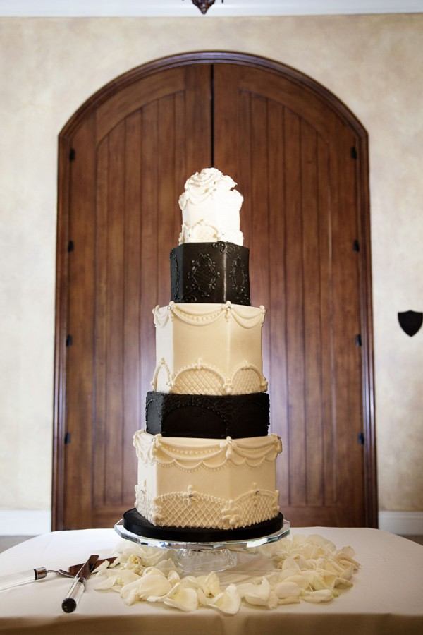 Diane wanted a black and white wedding cake - inspired by one of her favorite celebrity weddings. The Southern Highlands Golf Club was lit with red lighting and featured floating candle centerpiece. Photo by www.altf.com.