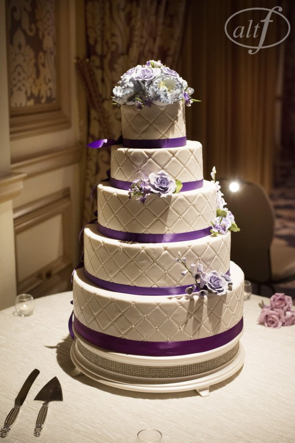 The five tiered wedding cake was wrapped in deep purple ribbon and featured sugar roses and tufted fondant.