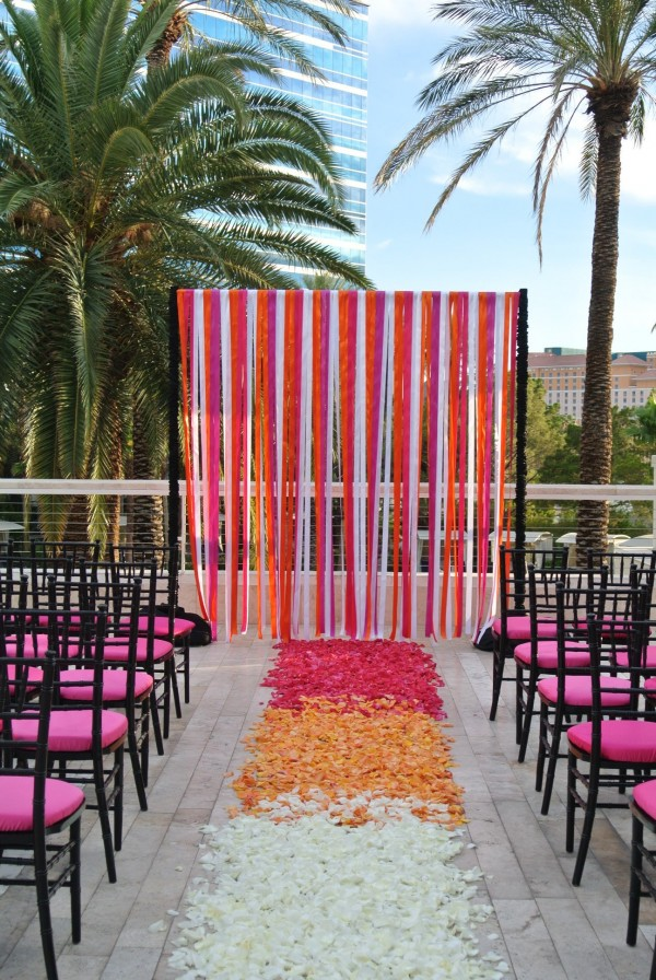 Just a little ombre aisle! Black Chiavari chairs with hot pink cushions and streamers tied the ceremony space together. Photo by Las Vegas Wedding Planner Andrea Eppolito.