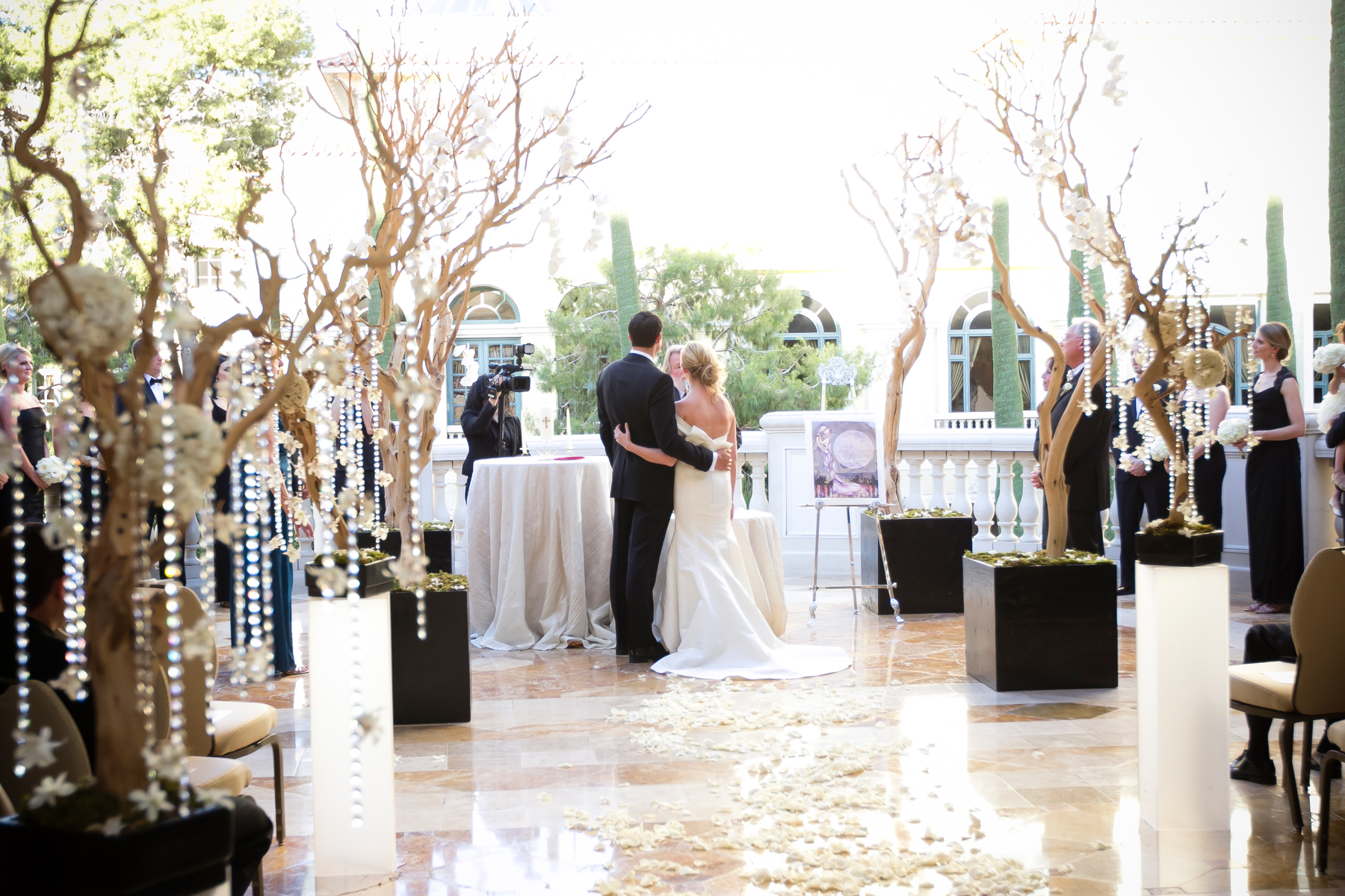 The bride and groom kept their arms around one another during the entire ceremony.  Wedding Venue: Bellagio Las Vegas.  Location: The Grand Patio. Flowers & Decor by Naakiti Floral . Photo by www.ronmiller.com . Las Vegas Wedding Planner: Andrea Eppolito Events .