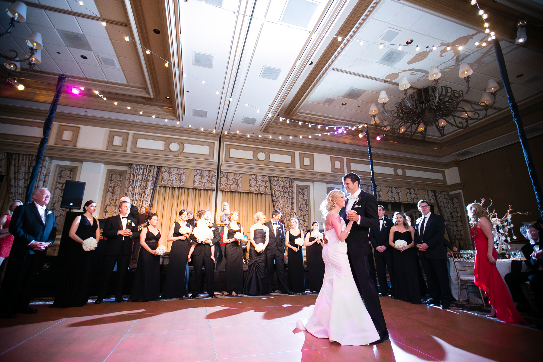 The first dance, surrounded by the bridal party, family, and friends.  Wedding Venue:  Bellagio Las Vegas.   Photo by  www.ronmiller.com .  Las Vegas Wedding Planner:  Andrea Eppolito Events .