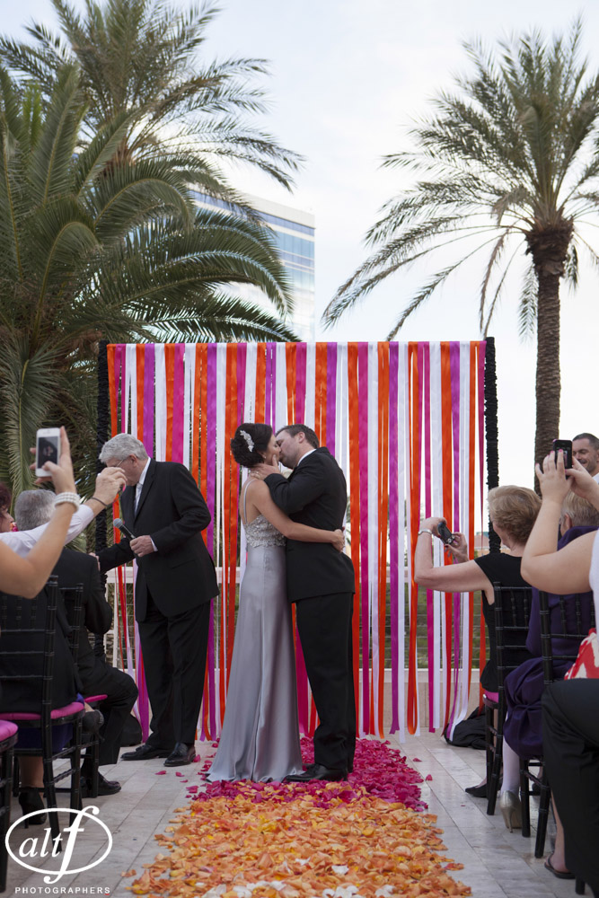 The first kiss - The ceremony was decorated in organ, pink, and white ribbons. The aisle was an ombre orange and pink rose petals. Las Vegas Wedding Planner Andrea Eppolito Events. LocationL Hard Rock Hotel Las Vegas. Photography by www.altf.com.