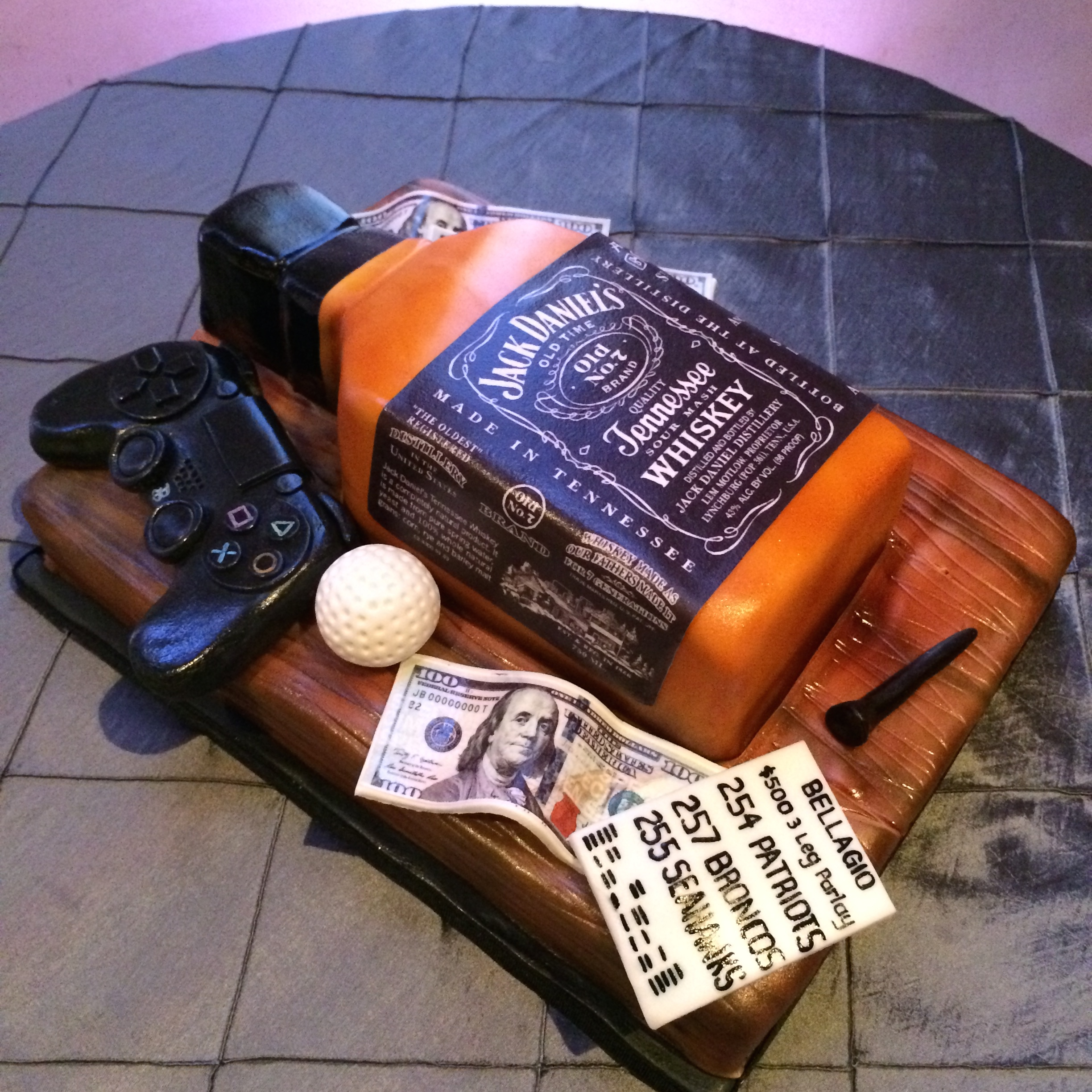 The groom's cake by Peridot Sweets featured gaming tickets, a bottle of Jack, and an old school video controller.   Las Vegas Wedding Planner: Andrea Eppolito | Wedding Venue: Westin Lake Las Vegas | Wedding Dress: Cosmobella | Floral and Decor: Naakiti Floral