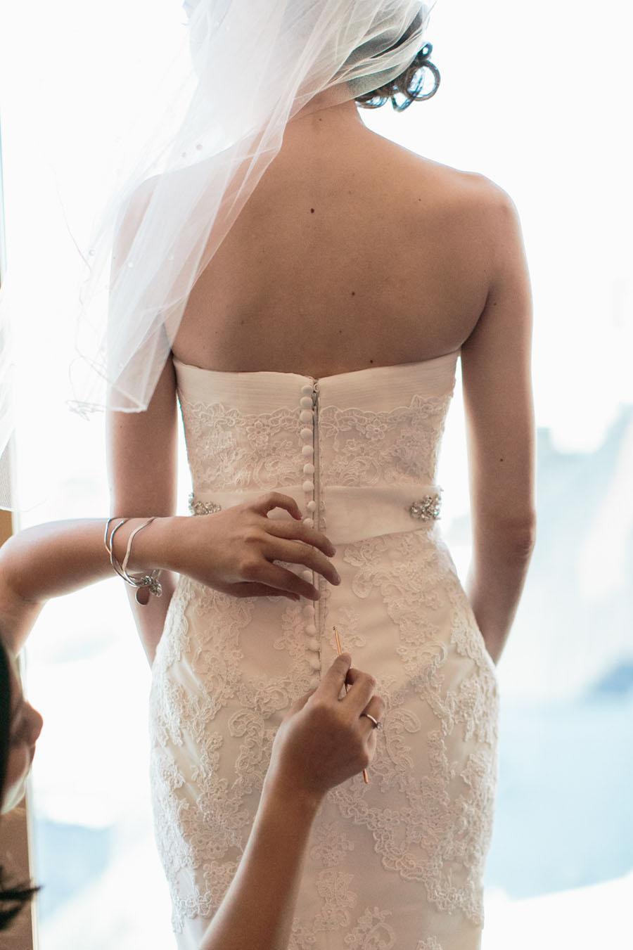 Katherine's wedding gown had a row of buttons down the back.  Each one was looped through individually by her maid of honor.    Las Vegas Wedding Planner  Andrea Eppolito .  Wedding at  Four Seasons .  Photography by  Meg Ruth .  Floral and Decor by  Naakiti Floral .