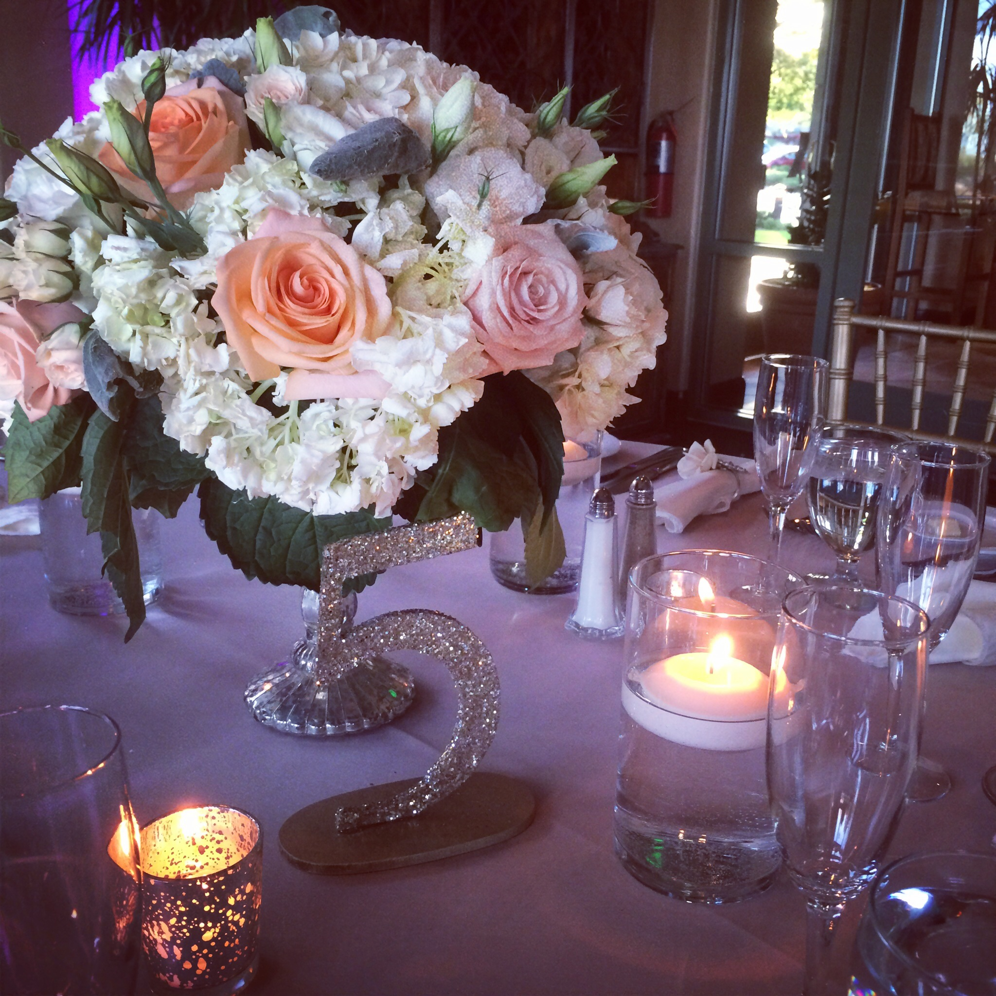 Tablescape of mocha linens, lush peach and white centerpieces, mercury glass voices, and glitter table numbers.Photo by Andrea Eppolito.  Las Vegas Wedding Planner Andrea Eppolito | Las Vegas Venue: Siena Golf Course |Floral & Decor: Naakiti Floral and Sit On This