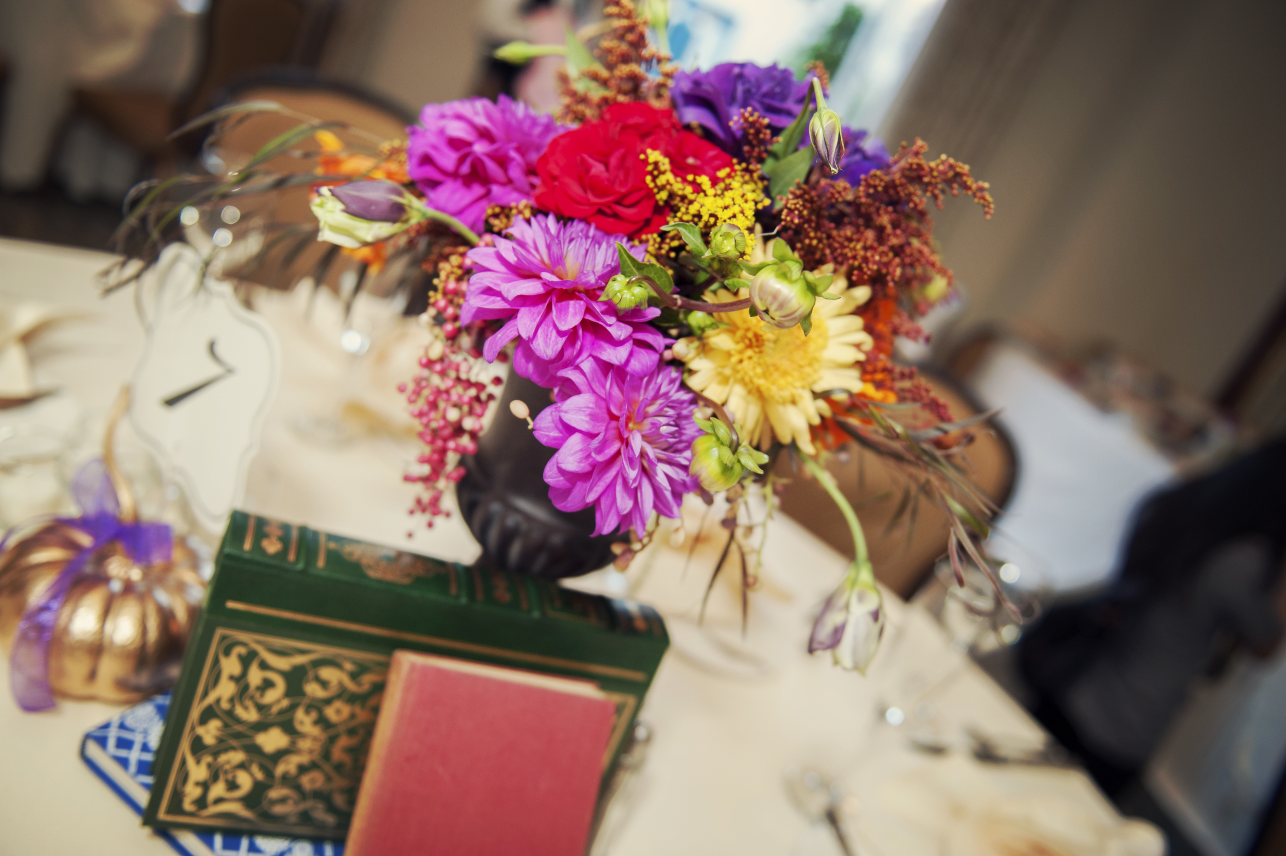 Jewel toned centerpieces celebrated the fall season, and gained hight and interest with little vignettes of books.    Destination Wedding Planner:   Andrea Eppolito Events   |  Historical Wedding Venue:   The Arizona Inn   |  Photography:  Raylene Streuber