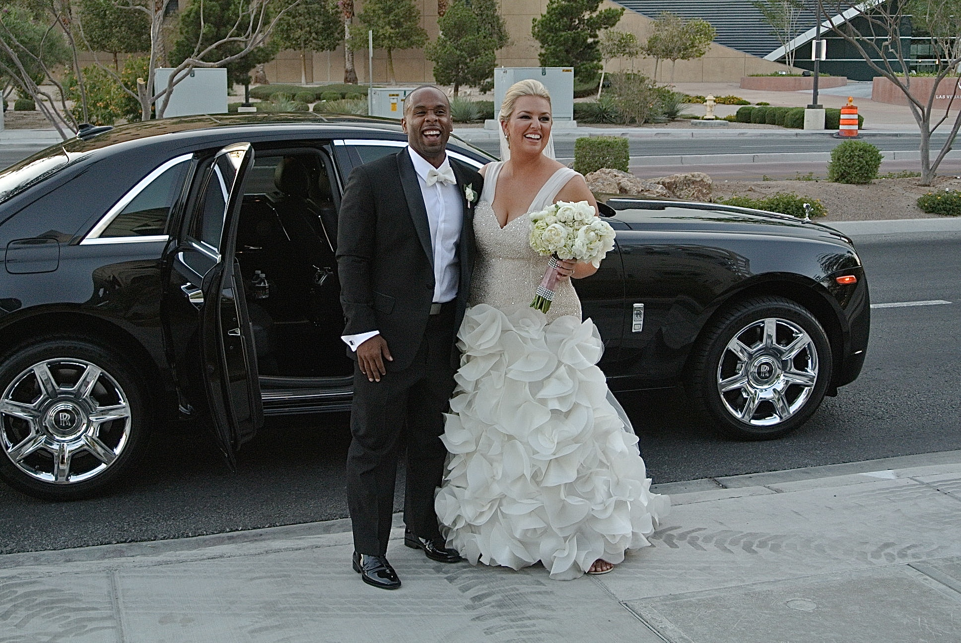 Looking for spectacular wedding transportation?  There is nothing like a timeless black Rolls Royce.  And you see those smiles?  All night long!!!    Las Vegas Wedding Planner Andrea Eppolito  |  Wedding at Keep Memory Alive Center  |  Floral and Decor by Naakiti Floral  |  Wedding Dress: Mina Olive