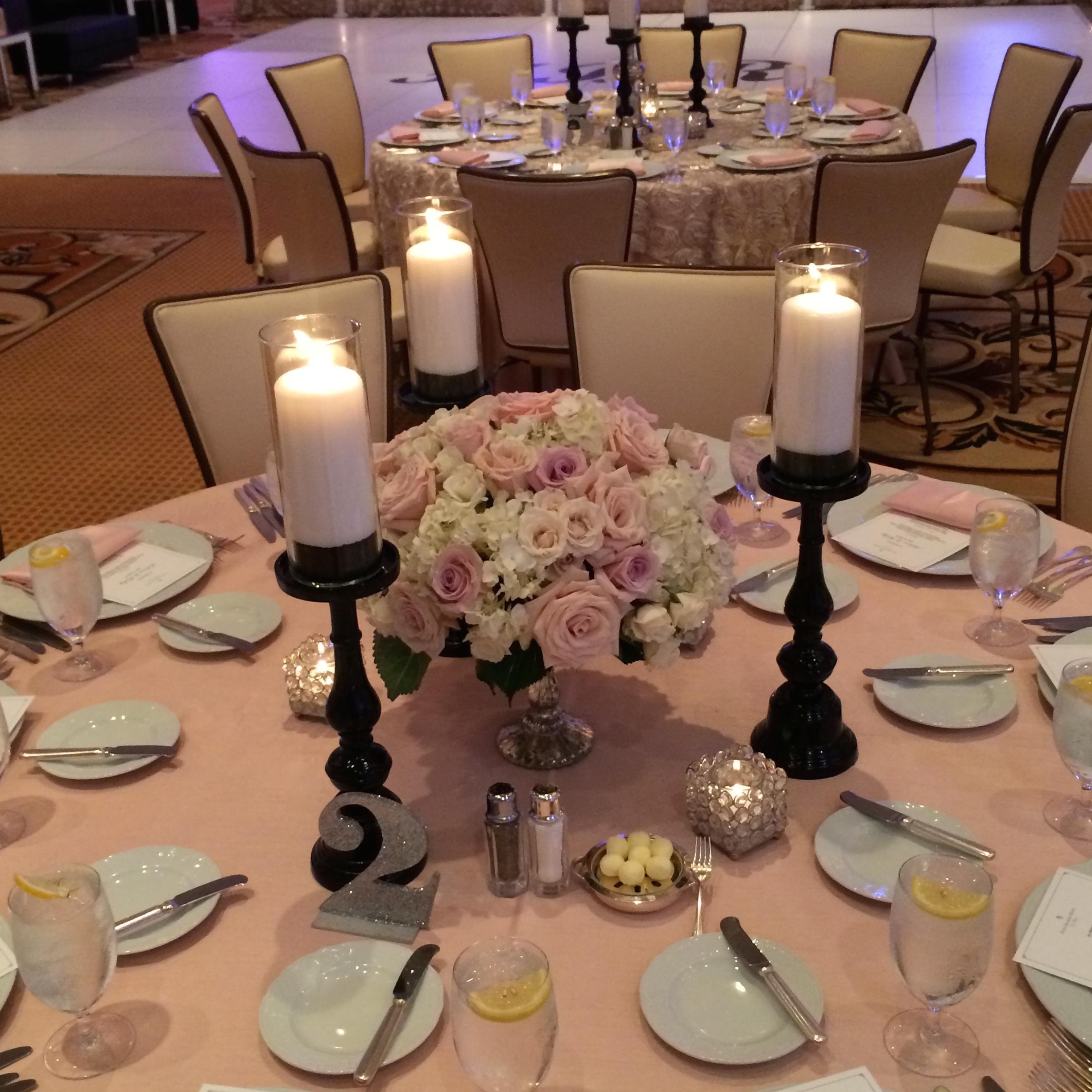 Low centerpieces of pink roses and ivory hydrangea were set off by black candle sticks and glitter table numbers. Flowers by  Naakiti Florals .
