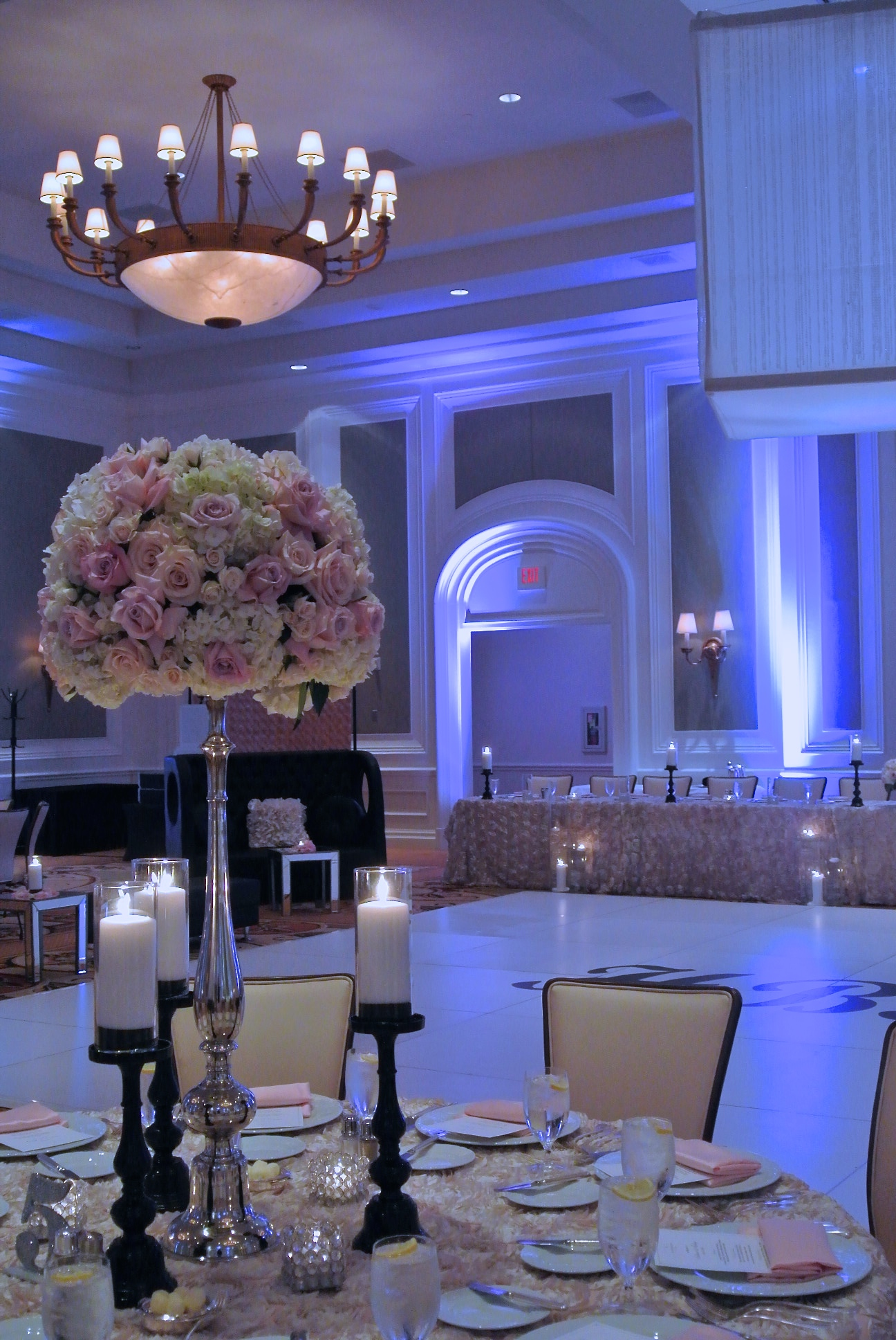 The second table scape design featured tall centerpieces on rosette linens, with back candles and smaller crystal votive holders. The long head table in the background shared the same linen and candle design elements. Naakiti Floral and Sit On This also provided the white dance floor, black monogram, and the crystal light box.