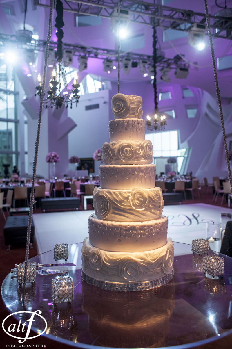 Everything about this wedding cake was epic!  From the seven tiers, each with a different flavor and filling, to the hand set Swarovski crystals, the fondant rosettes, and the hand etched design was magnificent.  Suspending the cake from the industrial AV rigging at the Keep Memory Alive Center, surrounding it with candles and chandeliers, and draping it in even more shimmering accents made this cake the showpiece of the eventing!   Wedding Cake by   Peridot Sweets  .  Photo by   AltF Photography  .